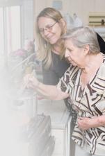 Carer helping elderly woman.