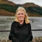 Head and body photo of Jane next to the loch at Arrochar. Cloudy sky. She is wearing a black top.