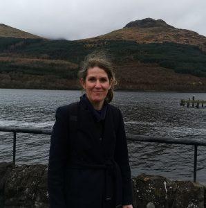Ailsa next to the loch in Arrochar. Cloudy sky. She is wearing black.