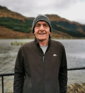 Head and body photo of Jamie. Standing next to the loch in Arrochar. Cloudy day. He is wearing a grey hat